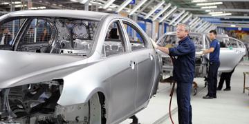 Trabajadores en cadena de montaje de vehículos