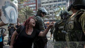 Una mujer se enfrenta a la policía antidisturbios durante una protesta contra el gobierno del presidente chileno, Sebastián Pinera, con carteles que representan unos ojos, en referencia a los manifestantes cuyos ojos han sido alcanzados por perdigones pol