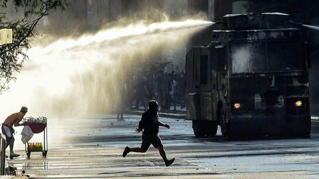 Un manifestante corre frente a un camión hidrante en Santiago, Chile, el 20 de diciembre de 2019