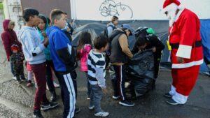 Niños migrantes reciben regalos de Navidad enviados por aficionados del equipo de fútbol FC Juárez, cerca del puente internacional Paso del Norte-Santa Fe, en Ciudad Juárez, México, el 25 de diciembre 2019