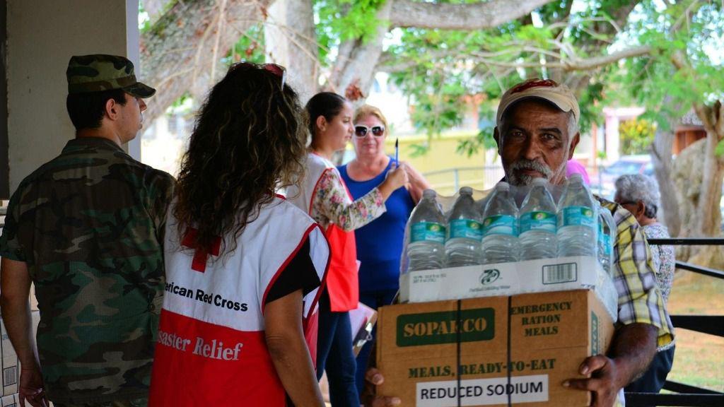 Un hombre recibe ayuda humanitaria por parte de la Cruz Roja tras el paso del huracán María por Puerto Rico