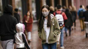 Una mujer camina con mascarilla para protegerse del brote del nuevo coronavirus