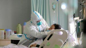 Un médico militar atiende a un paciente enfermo de coronavirus en la unidad de cuidados intensivos, en China