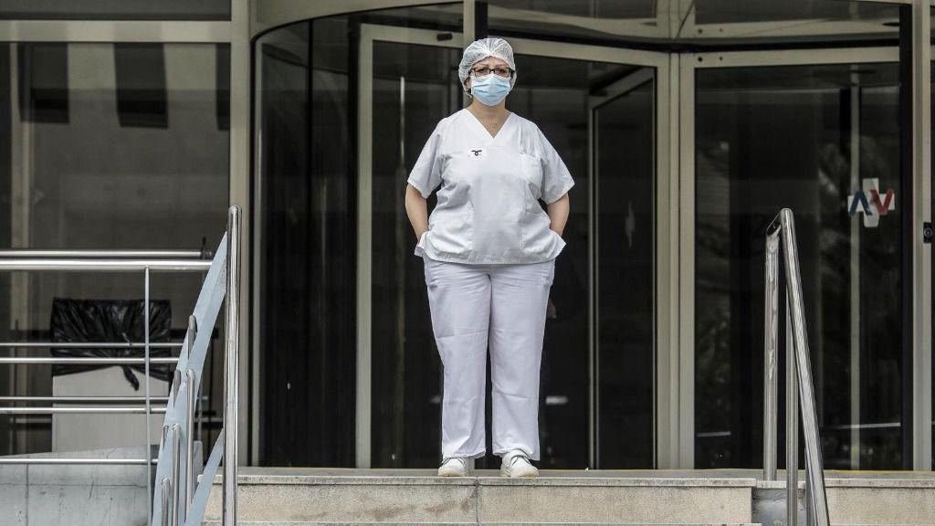 Sanitaria protegida con mascarilla y gorro durante el minuto de silencio en la entrada del Hospital Doctor Peset