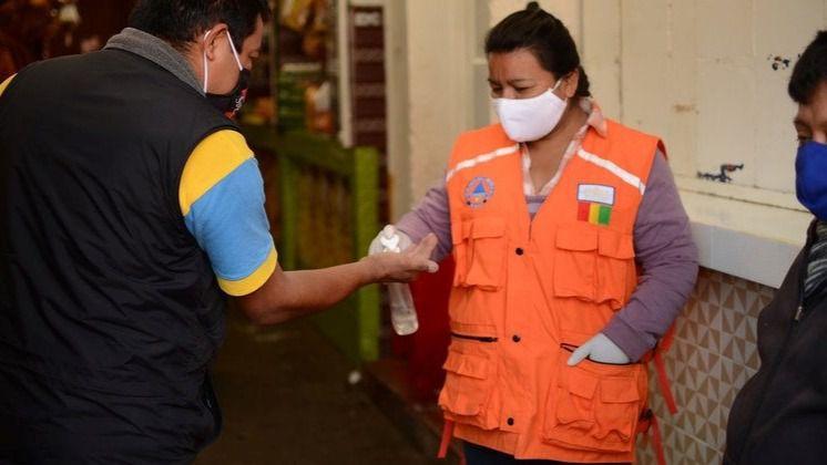 Una mujer aplica desinfectante de manos a un cliente a la entrada de un mercado municipal en la ciudad guatemalteca de San Marcos