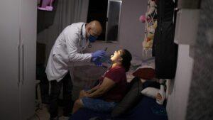 Un profesional de la salud examina a una mujer en su casa de Sao Paulo para averiguar si es un caso más de coronavirus en Brasil