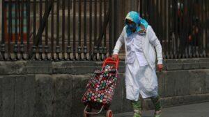 Una mujer con mascarilla y bata en una calle de México