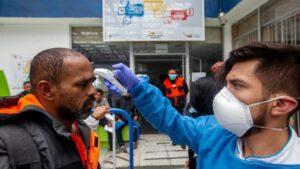 Médico ecuatoriano toma la temperatura a un hombre en la frontera con Colombia