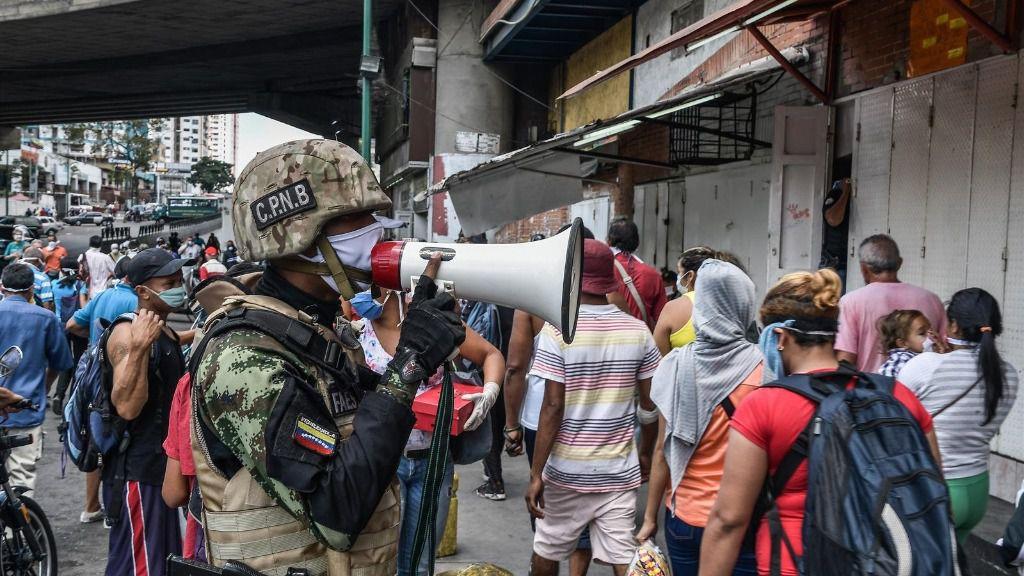 Un agente de la Fuerza Boliviariana de Venezuela explica a la población que debe regresar a sus hogares a causa de la cuarentena decetada por el Gobierno