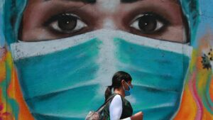 Una mujer camina por las calles de Ciudad de México frente a un mural pintado en homenaje a los trabajadores de la salud durante la pandemia de la COVID-19