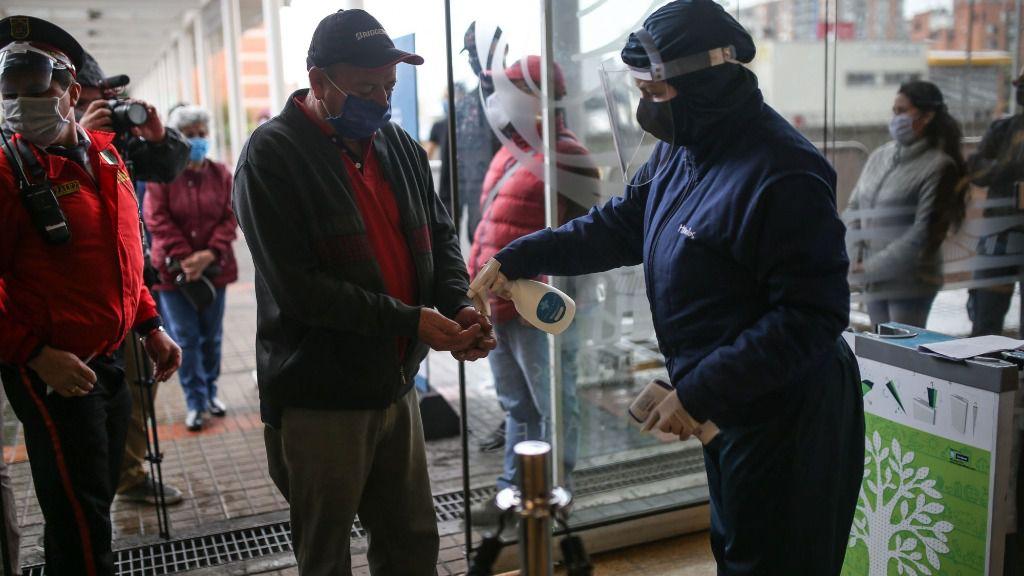 Una personas es rociada con gel desinfectante antes de ingresar en eun centro comercial de Bogotá, Colombia
