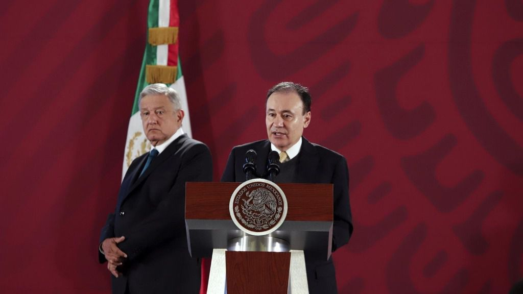 El presidente de México, Andrés Manuel López Obrador (izqda) escucha el discurso del secretario de Seguridad, Alfonso Durazo