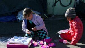 Niños migrantes con juguetes que recibieron como regalo de Navidad y que fueron enviados por aficionados del equipo de fútbol FC Juárez, cerca del puente internacional Paso del Norte-Santa Fe, en Ciudad Juárez, México, el 25 de diciembre de 2019