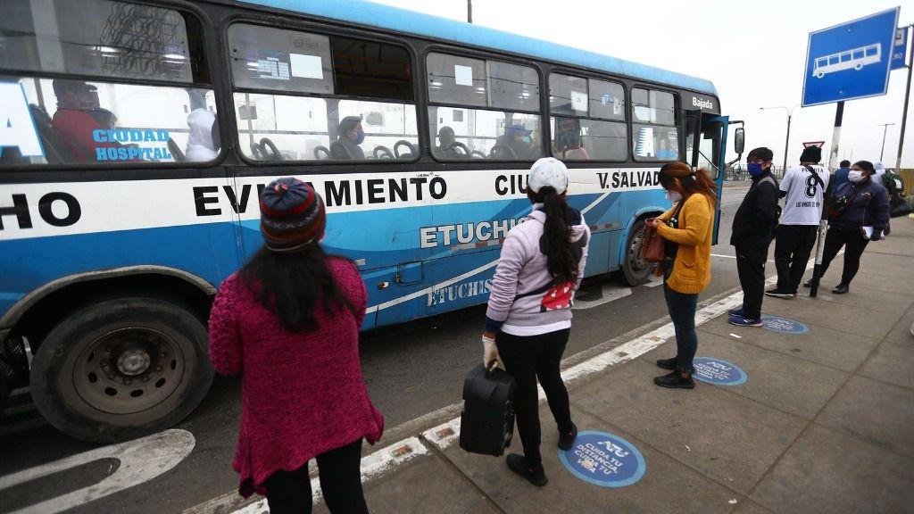 Un grupo de personas mantienen las distancias sociales mientras esperan en una parada de autobús de Lima, Perú