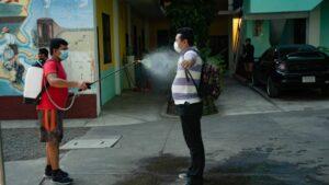 Un migrante hondureño es desinfectado tras su llegada Guatemala en plena pandemia